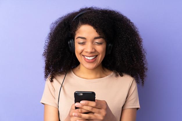 Junge afroamerikanerfrau lokalisiert auf lila wand, die musik hört und auf handy schaut