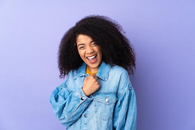 Junge afroamerikanerfrau lokalisiert auf purpur, der einen sieg feiert