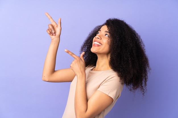 Junge afroamerikanerfrau lokalisiert auf purpur, der mit dem zeigefinger eine große idee zeigt
