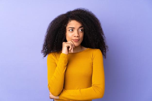 Junge afroamerikanerfrau lokalisiert auf purpur, der zweifel und denken hat