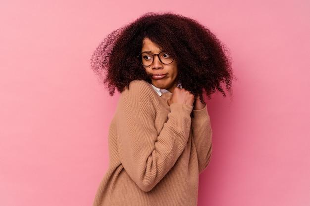 Junge afroamerikanerfrau lokalisiert auf rosa ängstlich und ängstlich.
