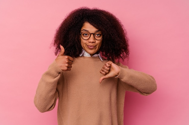 Junge afroamerikanerfrau lokalisiert auf rosa hintergrund, der daumen oben und daumen unten zeigt, schwieriges auswahlkonzept