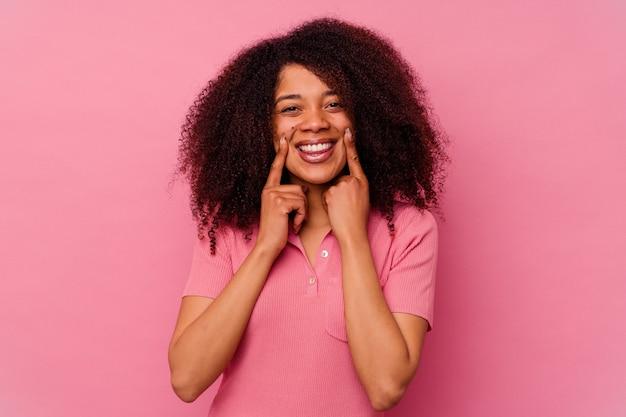 Junge afroamerikanerfrau lokalisiert auf rosa lächeln, finger auf mund zeigend.