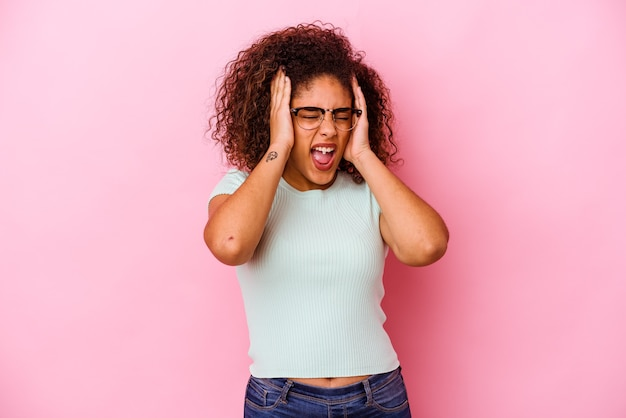 Junge afroamerikanerfrau lokalisiert auf rosa wand, die ohren mit händen bedeckt, die versuchen, nicht zu lautes geräusch zu hören