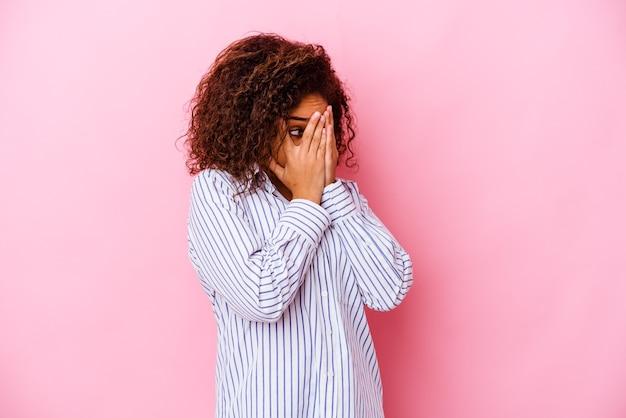 Junge afroamerikanerfrau lokalisiert auf rosa wandblinzeln durch erschrockene und nervöse finger.