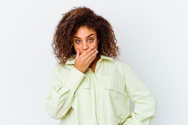 Junge afroamerikanerfrau lokalisiert auf weißem hintergrund, der den mund mit den händen bedeckt, die besorgt schauen.