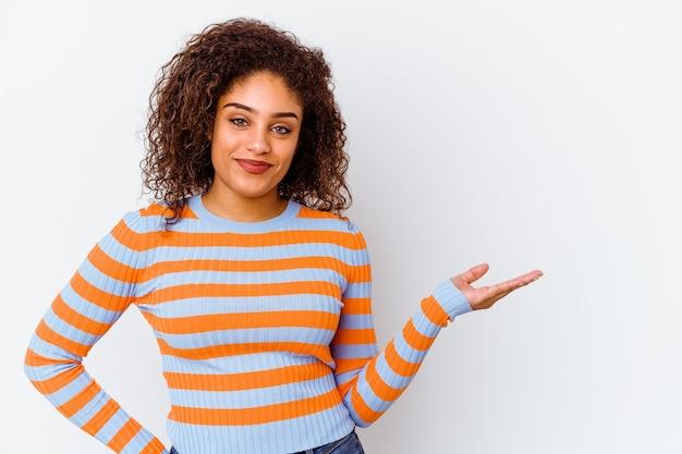 Junge afroamerikanerfrau lokalisiert auf weißem hintergrund, der einen kopienraum auf einer palme zeigt und eine andere hand auf taille hält.
