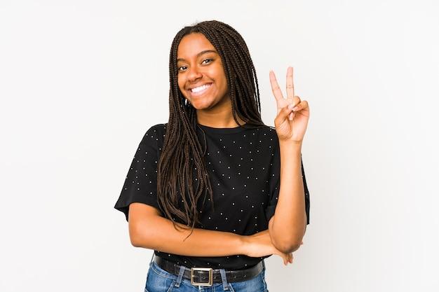 Junge afroamerikanerfrau lokalisiert auf weißem hintergrund, der nummer zwei mit den fingern zeigt.
