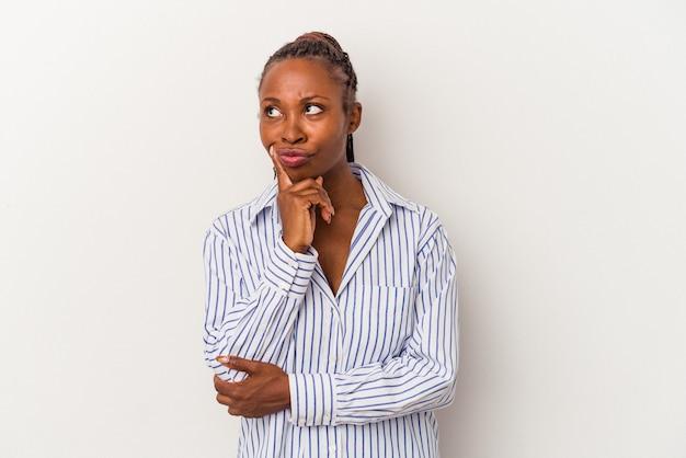 Junge afroamerikanerfrau lokalisiert auf weißem hintergrund, der seitlich mit zweifelhaftem und skeptischem ausdruck schaut.