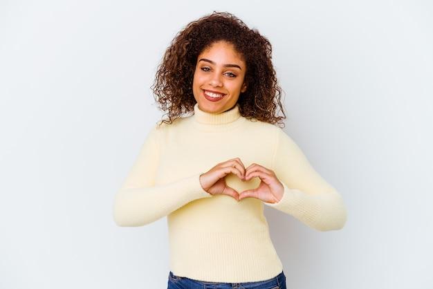Junge afroamerikanerfrau lokalisiert auf weißem hintergrund, die eine herzform mit den händen lächelt und zeigt.