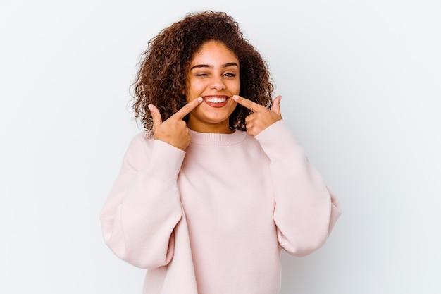 Junge afroamerikanerfrau lokalisiert auf weißem hintergrund lächelt und zeigt finger auf mund.