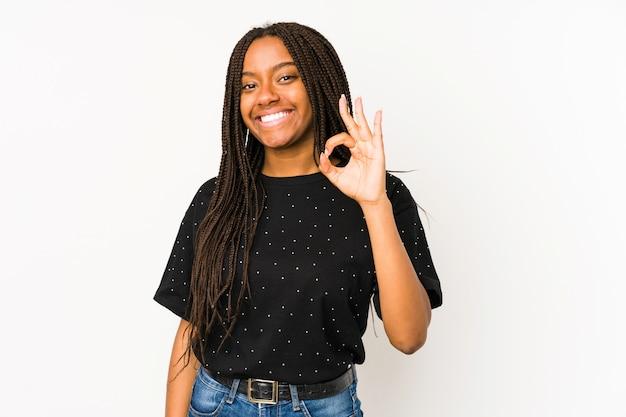 Junge afroamerikanerfrau lokalisiert auf weißer wand fröhlich und zuversichtlich, ok geste zeigend.