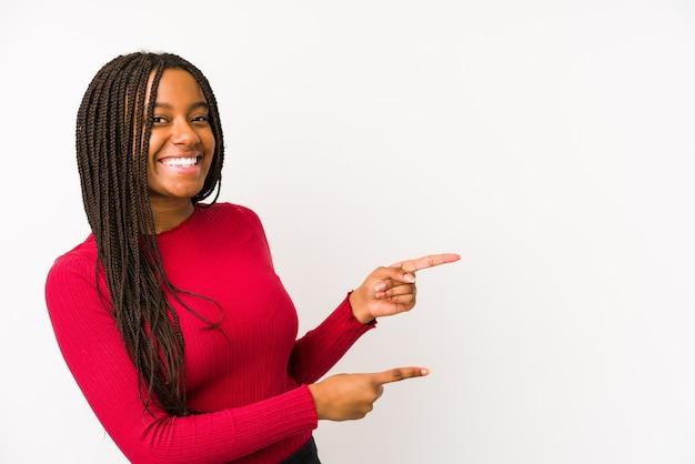 Junge afroamerikanerfrau lokalisiert aufgeregtes zeigen mit zeigefingern weg.