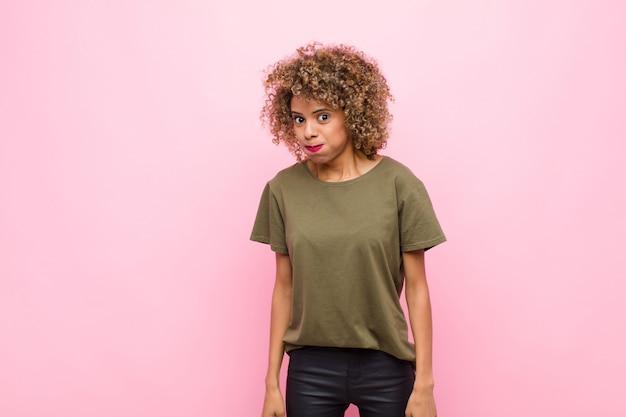 Junge afroamerikanerfrau mit einem albernen, verrückten, überraschten ausdruck, puffwangen, sich gestopft, fett und voller nahrung gegen rosa wand fühlen