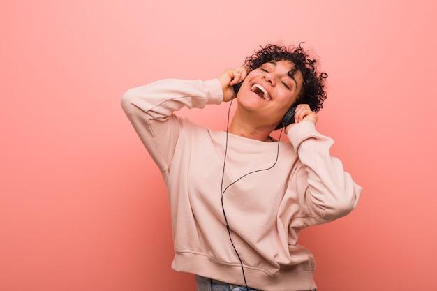 Junge afroamerikanerfrau mit einem muttermal, das musik mit einem kopfhörer tanzt und hört