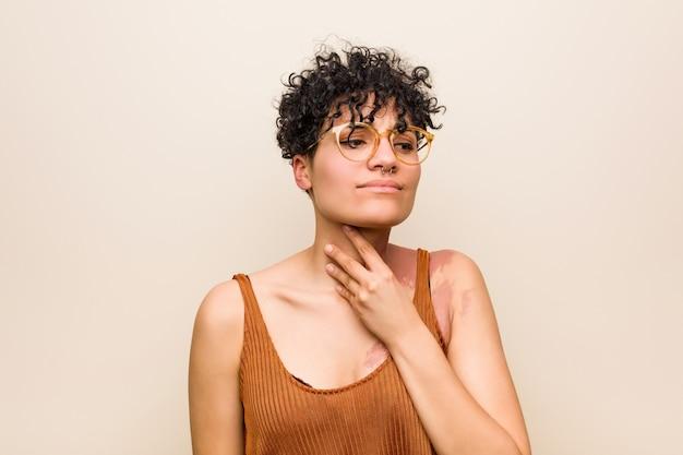 Junge afroamerikanerfrau mit hautgeburtsmarke leidet die schmerz in der kehle wegen eines virus oder einer infektion.