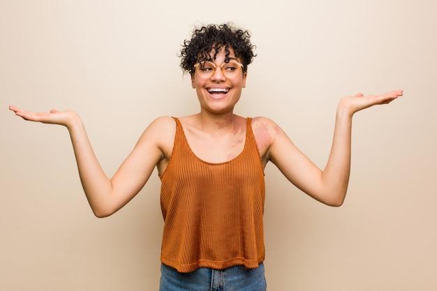 Junge afroamerikanerfrau mit hautgeburtsmarke macht skala mit den armen, fühlt sich glücklich und überzeugt.