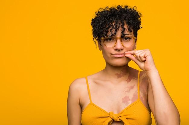 Junge afroamerikanerfrau mit hautgeburtsmarke mit den fingern auf den lippen, die ein geheimnis halten.