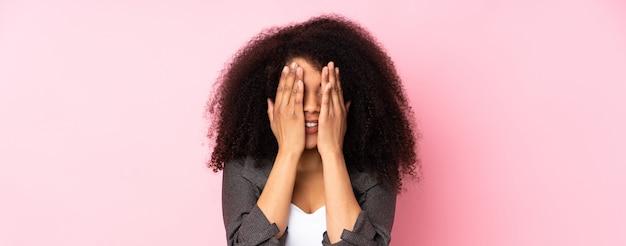 Junge afroamerikanerfrau über isolierten wandbedeckungsaugen durch hände