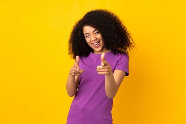 Junge afroamerikanerfrau über isolierter wand, die nach vorne zeigt und lächelt