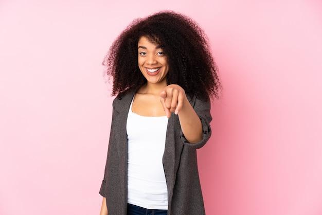 Junge afroamerikanerfrau über isolierter wand überrascht und nach vorne zeigend