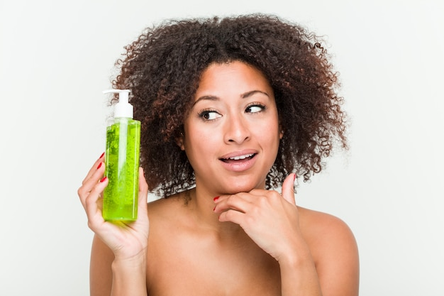 Junge afroamerikanerfrau, welche die aloe vera-flasche seitlich schaut mit zweifelhaftem und skeptischem ausdruck hält.
