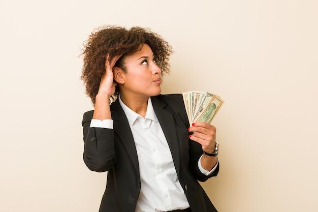 Junge afroamerikanerfrau, welche die dollar versuchen, einen klatsch zu hören hält.