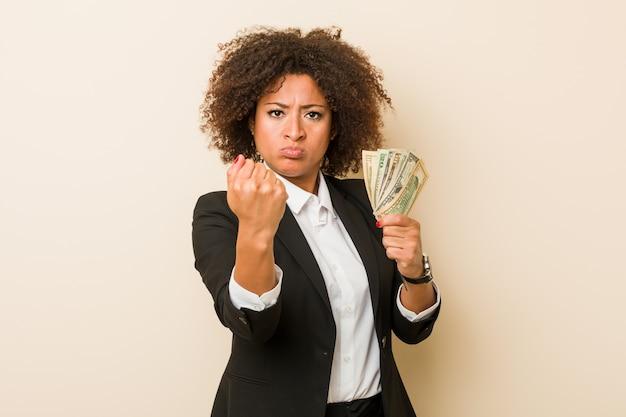 Junge afroamerikanerfrau, welche die dollar zeigen faust zur kamera, aggressiver gesichtsausdruck hält.