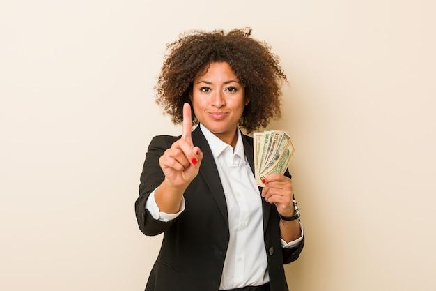 Junge afroamerikanerfrau, welche die dollar zeigen nummer eins mit dem finger hält.