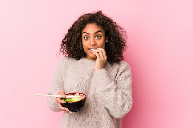 Junge afroamerikanerfrau, welche die nudeln beißen die fingernägel, nervös und sehr besorgt isst.