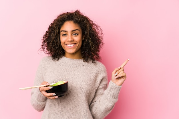 Junge afroamerikanerfrau, welche die nudeln lächeln und beiseite zeigen, etwas auf leerstelle zeigend isst.