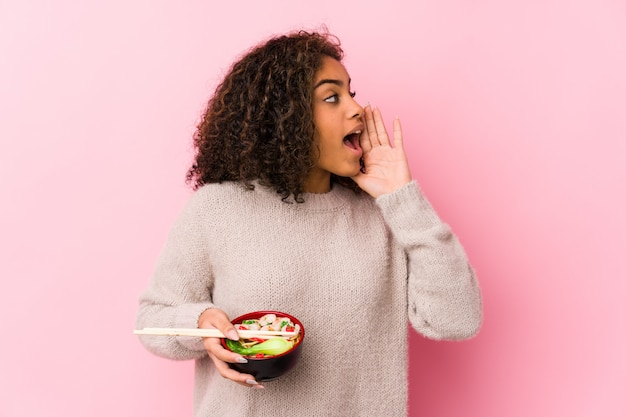 Junge afroamerikanerfrau, welche die nudeln schreien und halten palme nahe geöffnetem mund isst.