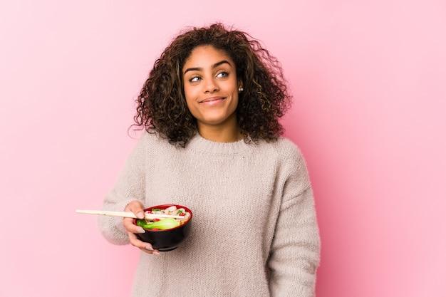 Junge afroamerikanerfrau, welche die nudeln träumen vom erreichen von zielen und von zwecken isst