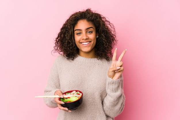 Junge afroamerikanerfrau, welche die nudeln zeigen nummer zwei mit den fingern isst.