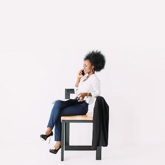 Junge afroamerikanergeschäftsfrau, die am telefon beim sitzen auf dem stuhl spricht