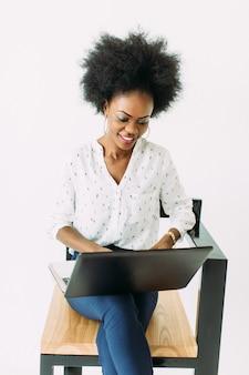 Junge afroamerikanergeschäftsfrau, die auf laptop beim sitzen auf dem stuhl, lokalisiert auf weiß schreibt