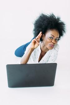Junge afroamerikanergeschäftsfrau, die den laptop beim lügen auf dem boden, lokalisiert verwendet