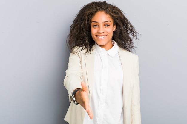 Junge afroamerikanergeschäftsfrau, die hand an der kamera in der grußgeste ausdehnt.
