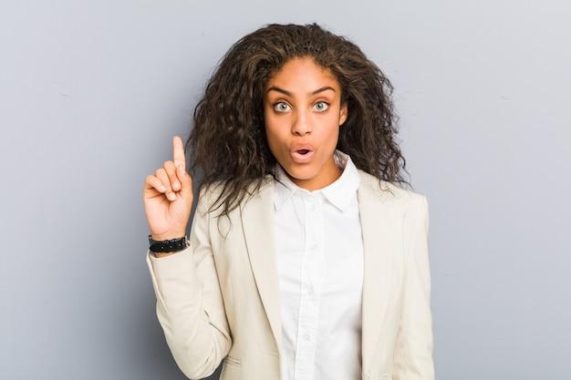 Junge afroamerikanergeschäftsfrau, die irgendeine großartige idee, konzept der kreativität hat.