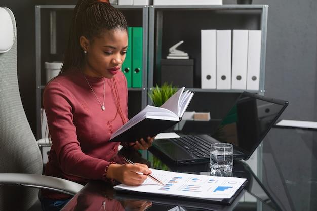 Junge afroamerikanergeschäftsfrau, die mit dokumenten und notizbuch am computertisch im büro arbeitet
