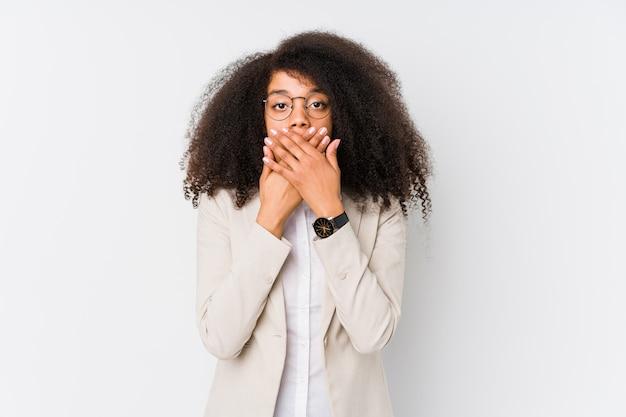 Junge afroamerikanergeschäftsfrau entsetzte bedeckungsmund mit den händen.