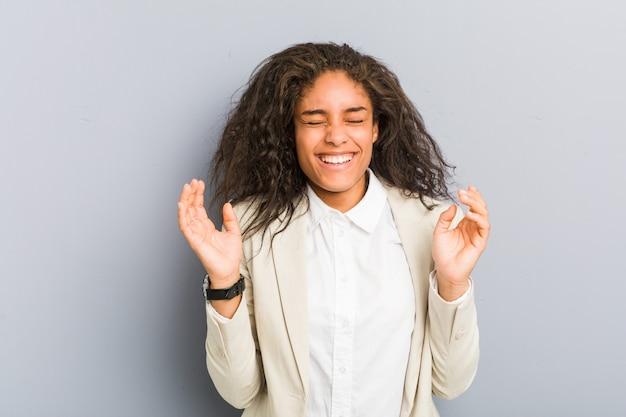 Junge afroamerikanergeschäftsfrau froh, viel lachend. glück-konzept.