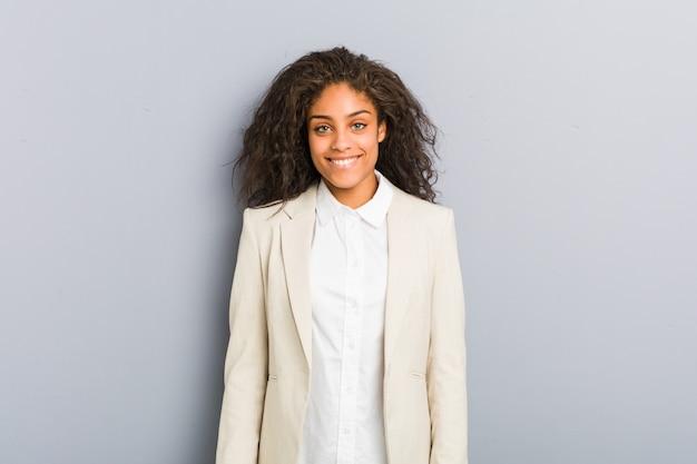 Junge afroamerikanergeschäftsfrau glücklich, lächelnd und nett.