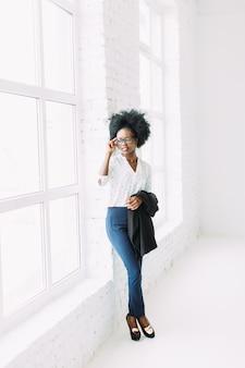 Junge afroamerikanergeschäftsfrau in den gläsern, stehend nahe dem großen fenster und halten jacke