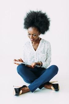 Junge afroamerikanergeschäftsfrau, welche die tablette beim sitzen auf dem boden, lokalisiert auf weiß verwendet