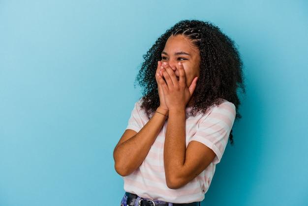 Junge afroamerikanerin auf blauem hintergrund isoliert, die über etwas lacht und den mund mit den händen bedeckt.
