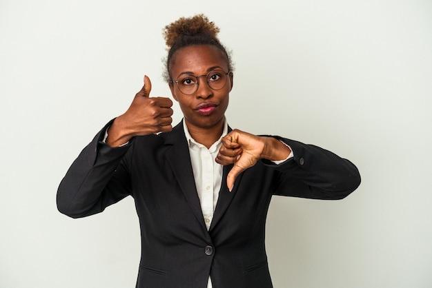 Junge afroamerikanerin des geschäfts isoliert auf weißem hintergrund mit daumen nach oben und daumen nach unten, schwieriges konzept zu wählen