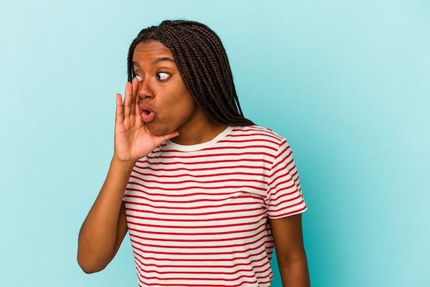 Junge afroamerikanerin, die auf blauem hintergrund isoliert ist, sagt eine geheime heiße bremsnachricht und schaut beiseite