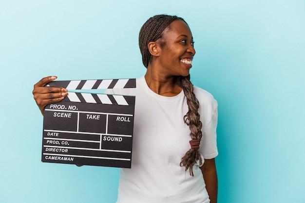 Junge afroamerikanerin, die auf blauem hintergrund isolierte klappe hält, sieht beiseite lächelnd, fröhlich und angenehm aus.