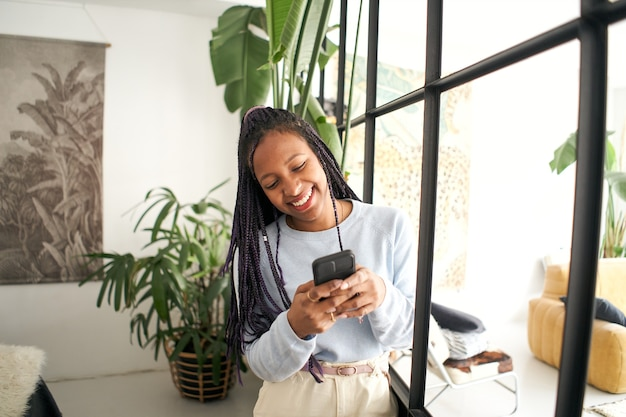 Junge afroamerikanerin, die auf ihrem smartphone lächelndes mädchen mit einem handy chattet